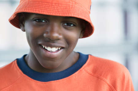 way of behaving: Portrait of a young boy in orange hat looking at camera