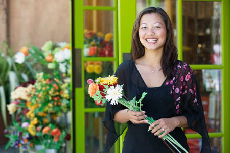 way of behaving: Portrait of a young woman smiling holding a bunch of flowers LANG_EVOIMAGES