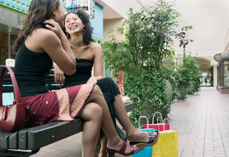 way of behaving: Two young women sitting together on a bench outdoors talking