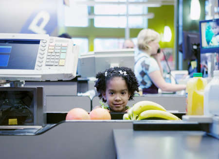 way of behaving: Portrait of a young girl standing at a super market checkout counter smiling