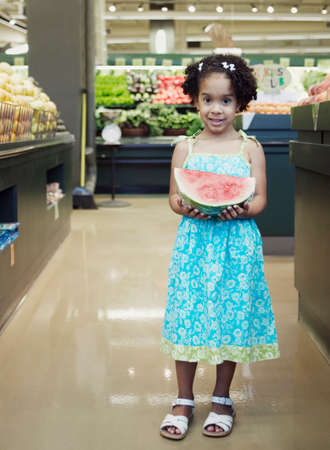 chirpy: Portrait of a young girl standing in a supermarket holding a cut watermelon LANG_EVOIMAGES