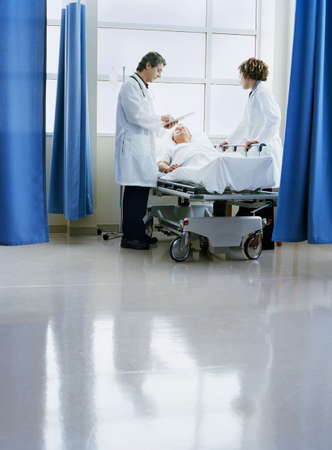 Doctors standing by a patients bed side in a hospital