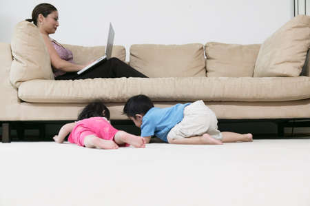 three persons only: Kids playing while mom works on laptop