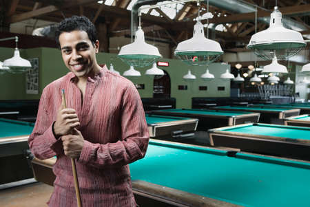 pool hall: Man holding a pool stick standing in a pool hall