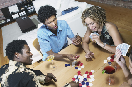 Group of people sitting at a table playing poker