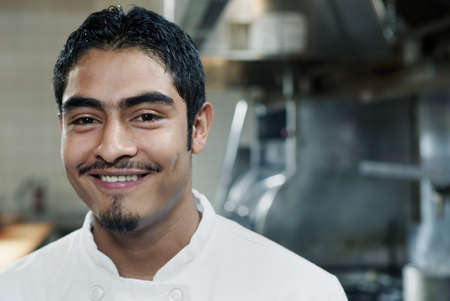 way of behaving: Portrait of a chef standing in a kitchen smiling
