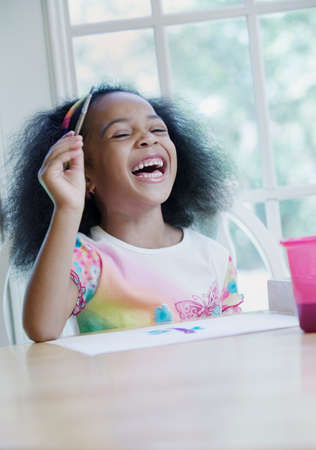 hold ups: Young girl seated at a table holding a paint brush laughing