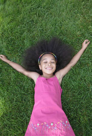 exalted: Young girl lying on grass smiling
