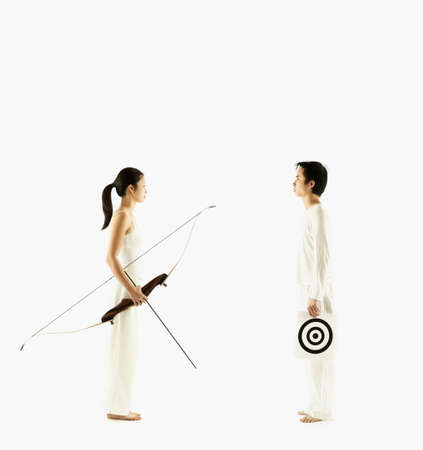 hauteur: Young woman holding a crossbow and a young man holding a target LANG_EVOIMAGES