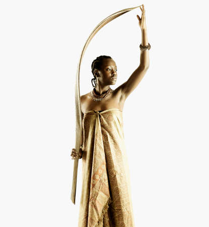 restfulness: Young tribal woman standing holding a wooden stick
