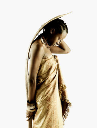 Side profile of a young tribal woman holding a wooden stick behind her back