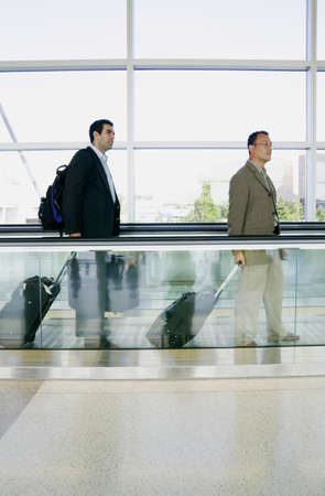 Side profile of two businessmen walking in an airport with luggage