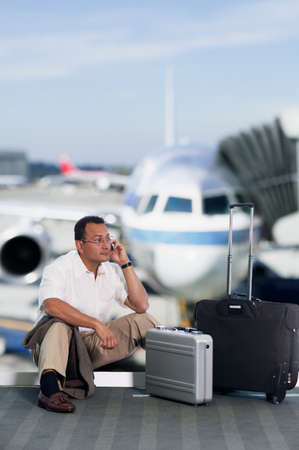 Businessman sitting on an airport floor and talking on a mobile phone