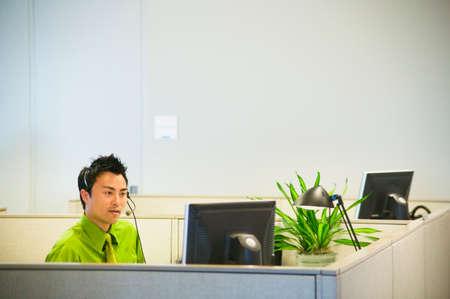 blithe: Hombre de negocios joven hablando en auriculares sentado frente a una pantalla de ordenador LANG_EVOIMAGES