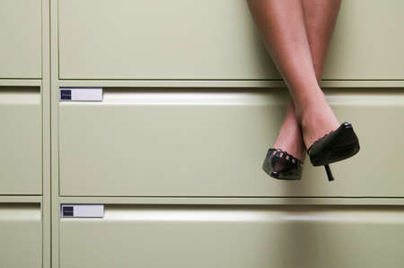 dangling: View of a womans legs dangling from a filing cabinet LANG_EVOIMAGES