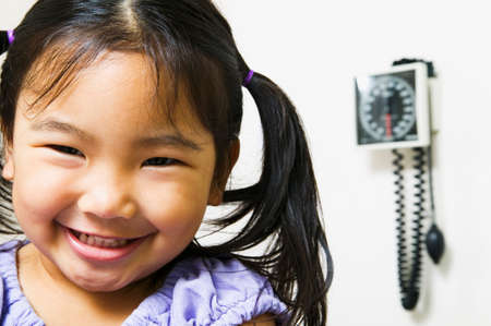 Young girl sitting in a doctors office smiling