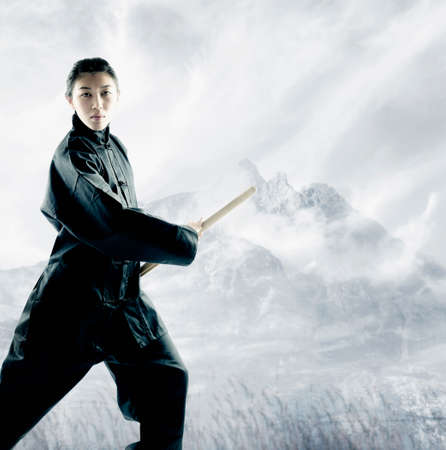 living being: Portrait of a young woman holding a wooden stick standing in a martial arts stance