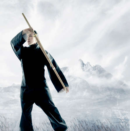 invariable: Portrait of a young woman holding a wooden stick standing in a martial arts stance