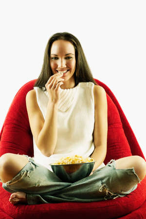 restfulness: Young woman sitting on a couch eating wafers from a bowl
