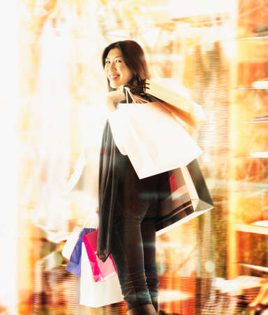 way of behaving: Young woman standing holding shopping bags LANG_EVOIMAGES