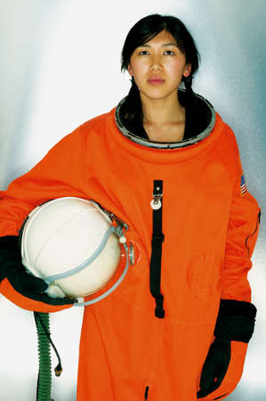 bullet camera: Portrait of a young female astronaut wearing a space suit holding space helmet LANG_EVOIMAGES