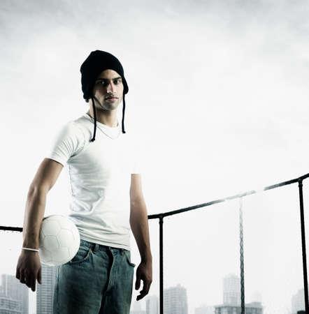 young man standing: Ritratto di un giovane uomo in piedi in possesso di una palla