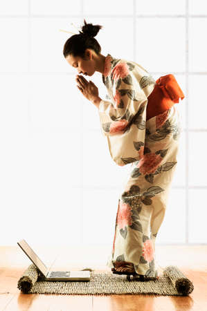 unawares: Side profile of a young woman wearing a kimono standing in front of a laptop LANG_EVOIMAGES