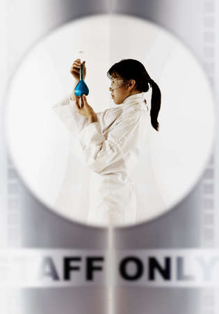 Side profile of a female scientist holding a beaker Stock Photo