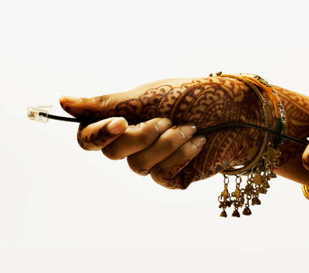 Womans henna decorated hand holding a telephone wire