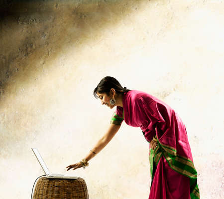 Young woman in a sari operating a laptop