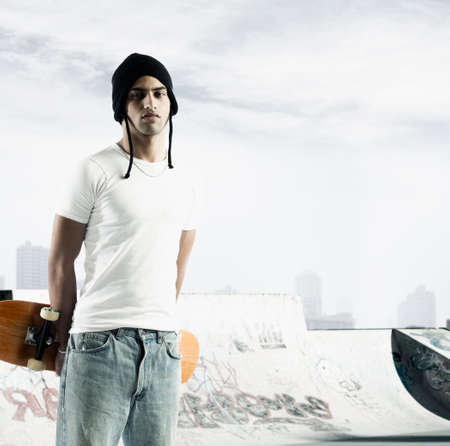 ultimatum: Portrait of a young man holding a skateboard looking at camera LANG_EVOIMAGES