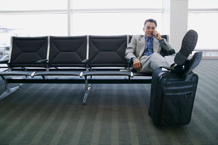 Businessman sitting in an airport lounge with feet up on a trolley LANG_EVOIMAGES