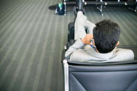 lounge: Rear view of a businessman talking on a mobile phone in an airport lounge