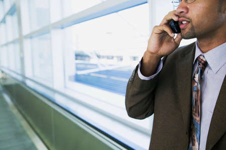 effrontery: Close-up of a young businessman talking on a mobile phone