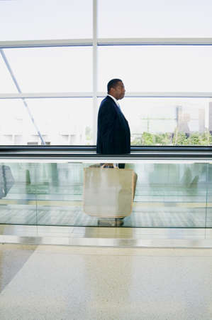 credence: Side profile of a businessman standing on an airport escalator with luggage