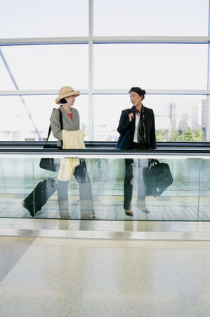 panache: Side profile of two young women standing on an airport escalator with luggage