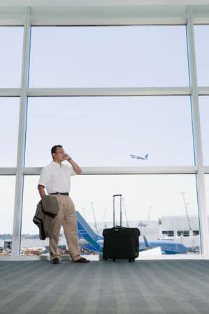 way of behaving: Businessman talking on a mobile phone in an airport LANG_EVOIMAGES