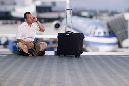 effrontery: Businessman sitting on an airport floor and talking on a mobile phone