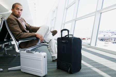 voyage: Portrait d'un jeune homme d'affaires assis dans un salon de l'aéroport avec des bagages regarder la caméra