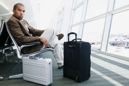 1 person: Portrait of a young businessman sitting in a airport lounge with luggage looking into the camera