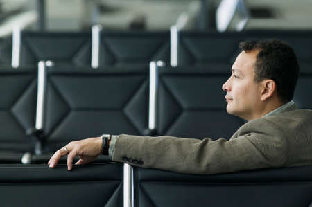 travelled: Side profile of a businessman sitting in an airport lounge LANG_EVOIMAGES