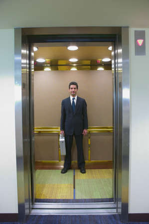 spanish ethnicity: Young businessman standing in an elevator with a briefcase