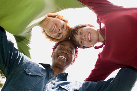 three persons only: Low angle view of three young women standing in a huddle