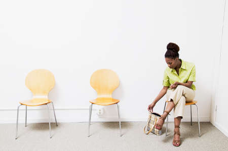 Businesswoman sitting on chair in a waiting room LANG_EVOIMAGES
