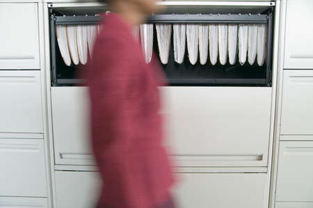 1 person: Businesswoman walking in an office by a filing cabinet