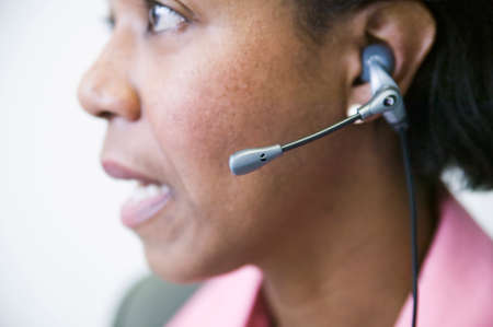 spanish ethnicity: Close-up of a businesswoman talking on a headset LANG_EVOIMAGES
