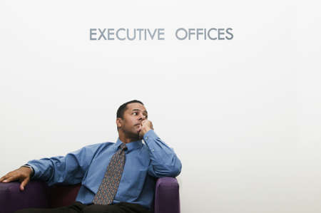 one mid adult man: Businessman sitting on a couch in an office with his hand on his chin