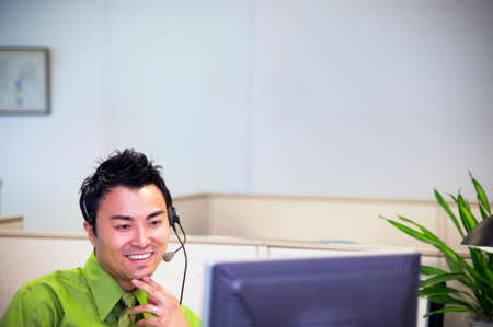 vietnamese ethnicity: Young businessman talking on headset sitting in front of a computer screen