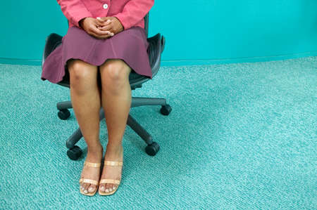 three persons only: Low section view of a businesswoman sitting on a chair LANG_EVOIMAGES