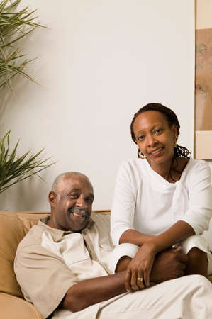 mid adult couple: Portrait of a mid adult couple sitting together on a sofa